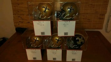 New Orleans Saints Authentic Mini Helmets in display cases.