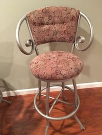2 like new wrought iron barstools    Custom upholstered.  Fabric purchased and sent in to company.  Matte silver finish. Swivel   Top of the line accents.  Covered buttons.  Upholstered backs. Accent wrought iron on feet and on support bars.   38 km