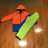 orange and blue zip-up hooded jacket and green pants