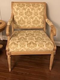 Brown wooden frame white floral padded armchair