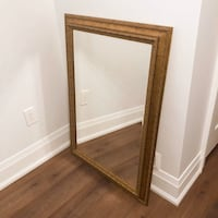 Gold framed mirror with ornate detail. Great condition
