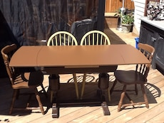 rectangular brown wooden dining table with four windsor chairs