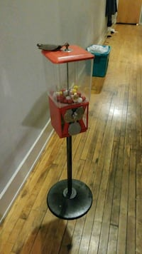 black and red gumball machine and stand