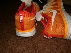 pair of white-and-orange Adidas low top sneakers