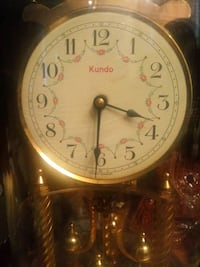 round gold analog watch with brown leather strap