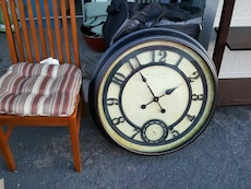 black and white analog round wall clock; brown wooden chair