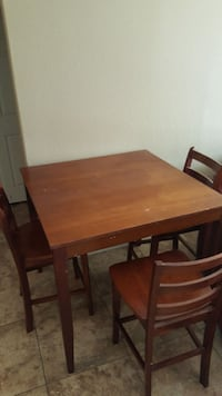 rectangular brown wooden table with 3 chairs