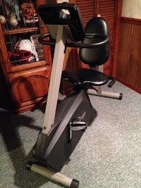 Full size metal exercise bike with black padded seat and back rest