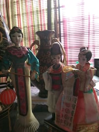 thee ceramic woman in different dresses