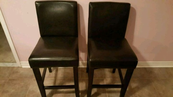 two black leather padded chairs counter height