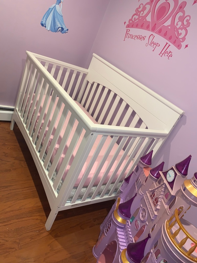Photo White wooden baby crib and mattress