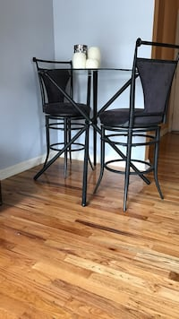 Round black glass top black metal base table with two chairs