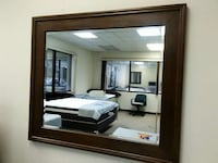 rectangular brown wooden framed wall mirror