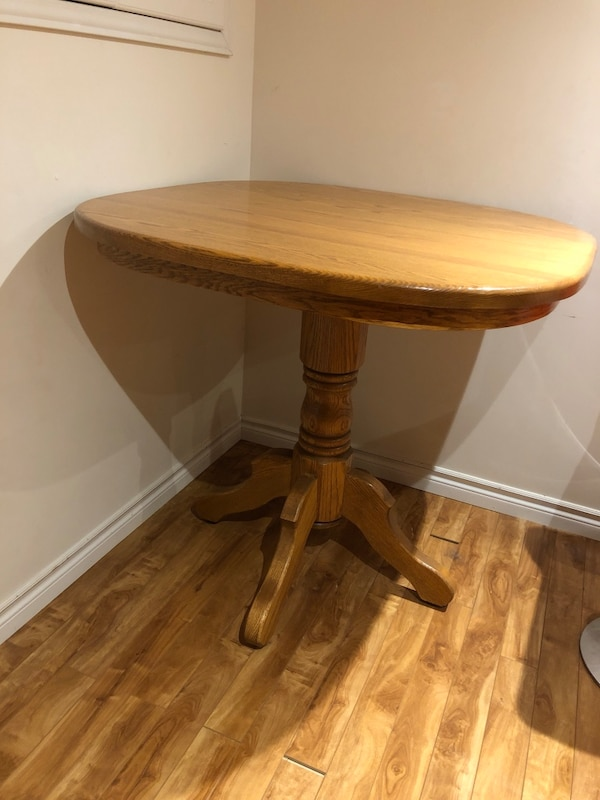 brown wooden round table with two chairs