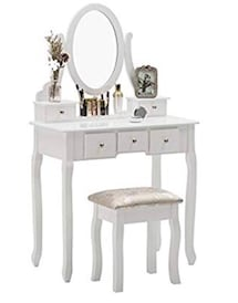 White vanity table set with oval mirror.