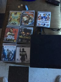 black Sony PS3 slim game console with assorted game cases Winnipeg, R3B 3C3