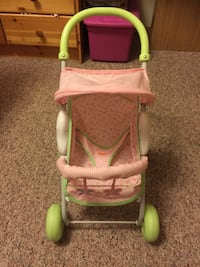 toddler's pink and green Fisher-Price stroller