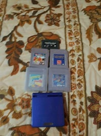 blue Nintendo DS with game cartridges