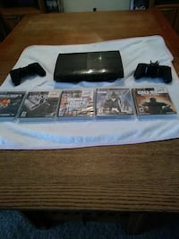 black Sony PS3 super slim console with two controllers and five game cases San Marcos, 92078