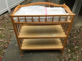 Brown wooden changing table with white mattress