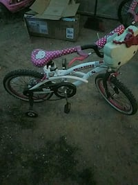 toddler's white and pink bicycle with training whe