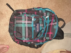 gray, blue, and red check Jansport backpack