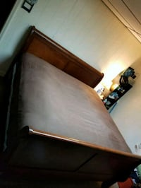 brown wooden bed frame with white mattress Raleigh