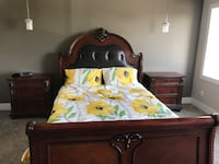 brown wooden bed frame with white and green floral bedspread Leduc
