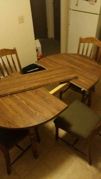 oval brown wooden table with four chairs dining set Medicine Hat, T1B 3M1