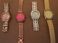 Four round analog watches with link bracelets