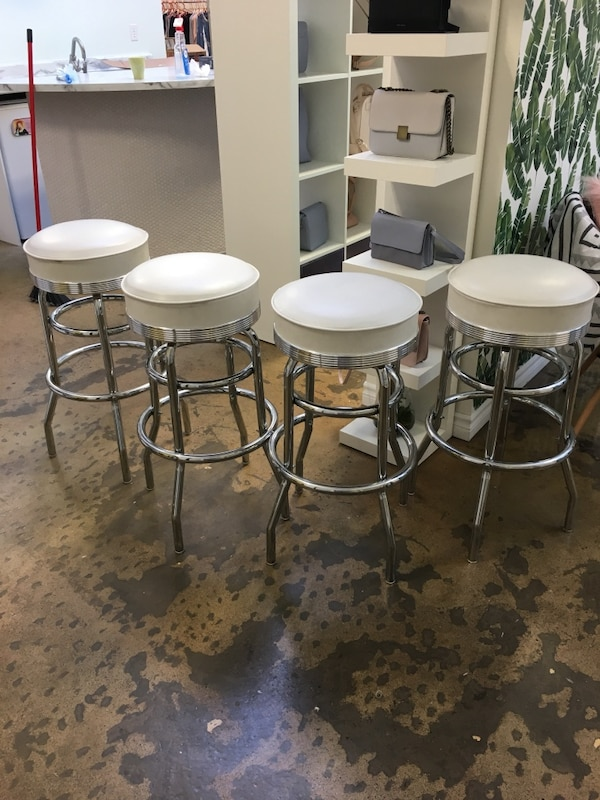 Four white leather padded bar stools