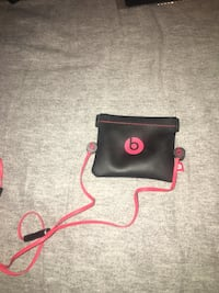black-and-red Beats earbuds with pouch