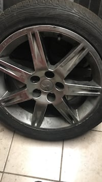 chrome Mitsubishi 7-spoke vehicle wheel with tire
