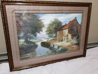 house near river beside tree painting with brown frame