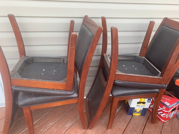 two brown wooden framed black leather padded chairs