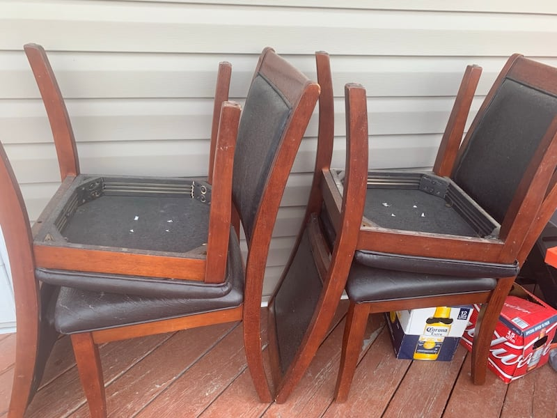 two brown wooden framed black leather padded chairs c9ef76a9-acf3-48c8-90d7-ad1ac4a7c951
