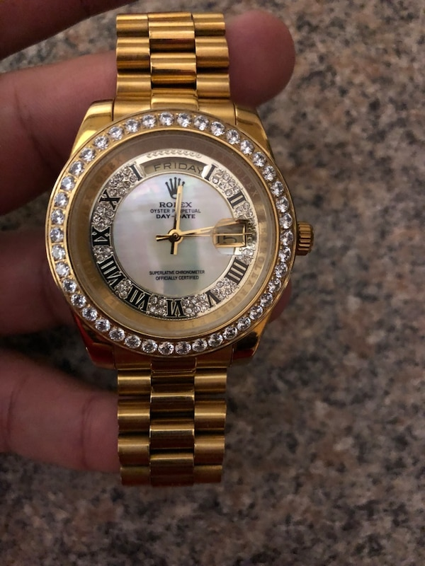 round gold Rolex analog watch with gold link bracelet