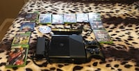Black xbox with controllers and game cases