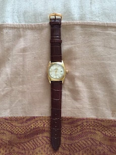 round gold framed analog watch with brown leather strap