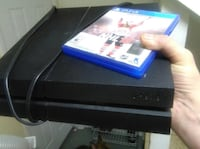 Black sony ps4 console with controller and nhl 16