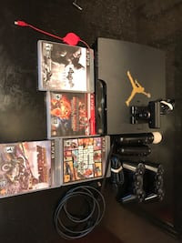 black Sony PS3 slim console with controllers and game cases