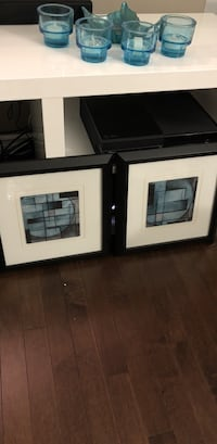 two blue abstract paintings with black frames