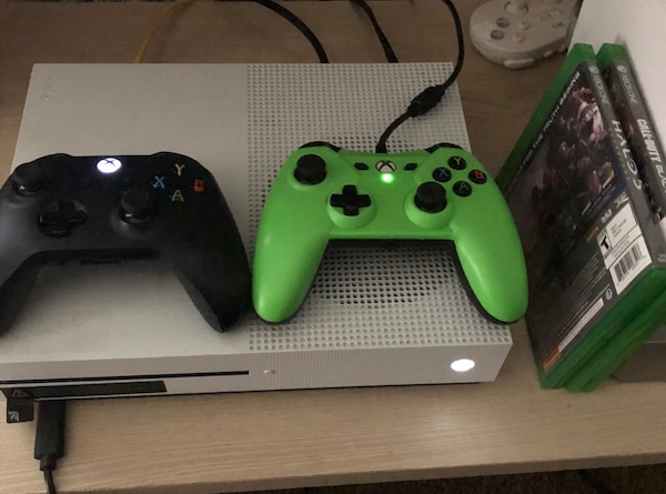 white Xbox One console with two controllers