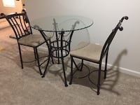round glass-top table with black metal base 7 mi