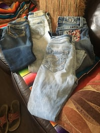 two blue and one gray denim jeans