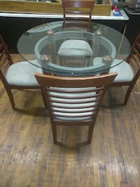 round glass top table with brown wooden base