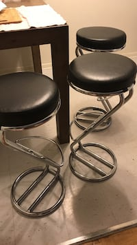 Three stainless steel and black stools
