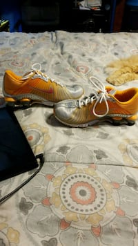 pair of orange-and-black Nike cleats Pearl, 39208