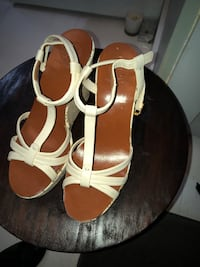 Pair of brown-and-white ankle-strap leather wedge sandals