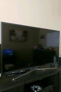 black flat screen TV with remote Los Angeles, 90011